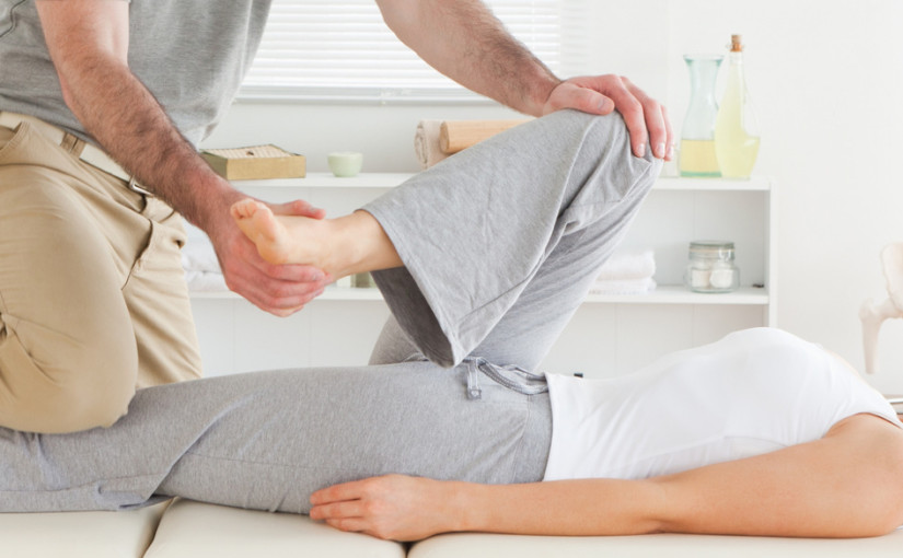 A physiotherapist is stretching a young woman's hip